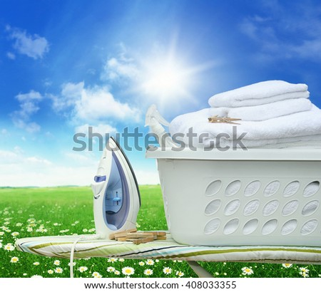 Iron board and iron with laundry basket in field of daisies - stock photo