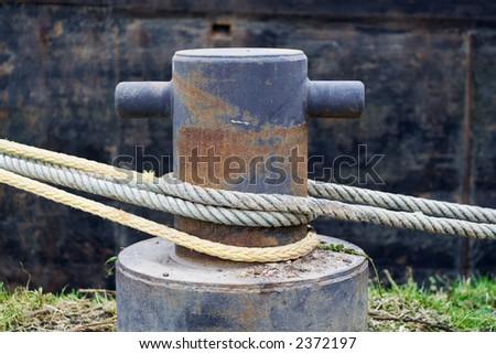 Iron bollard with ship ropes. - stock photo