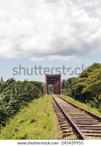 Iron bridge in a train railroad in a tropical country featuring a beautiful blue sky and an exhuberant vegetation - stock photo