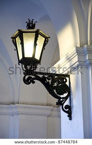 Iron cast street light illuminating old arches - stock photo