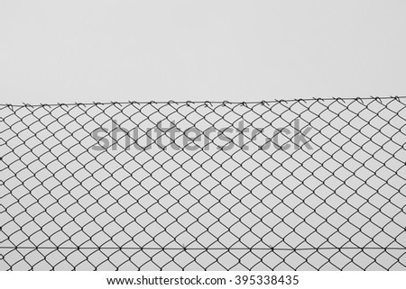 Iron chain link fence wire netting with diamond mesh pattern abstract background. Black and white. - stock photo
