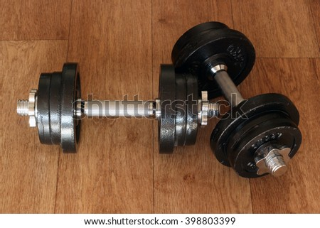 Iron dumbbells on hardwood floor. Weightlifting training concept.