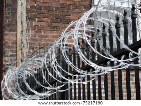 Iron fence with razor and barbed wire - stock photo