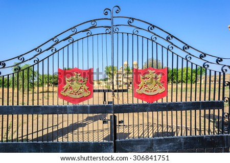 Iron gate and coat of arms of a Palace of Jaisalmer, Rajasthan, India with insignia and copy space - stock photo