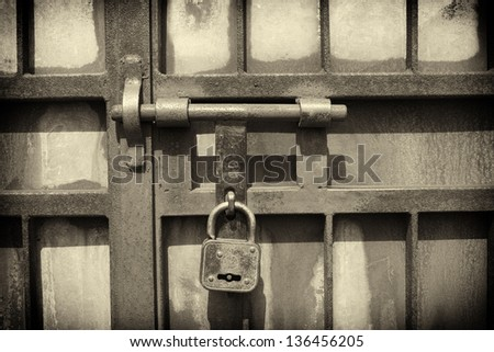 iron latch and padlock  in sepia tone - stock photo