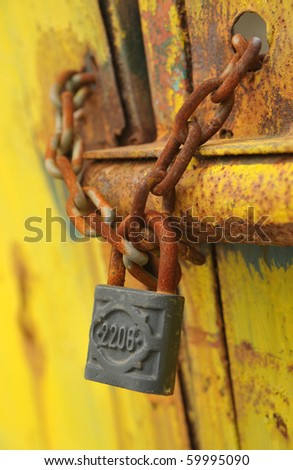 Iron lock and chain on an old rusty door - stock photo