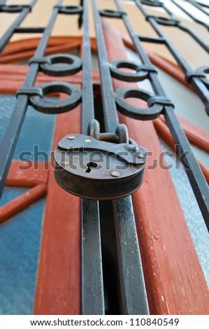 Iron lock hangs on a lattice before door - stock photo