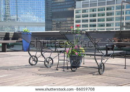 Iron Lounge Chairs on Outdoor Rooftop Deck in Urban City - stock photo