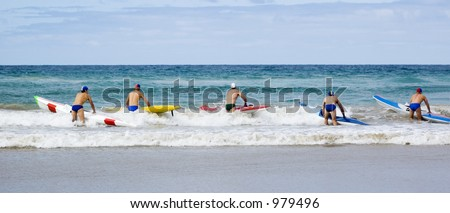 Iron men line up along the beach ready to start a race on their surf skis. - stock photo
