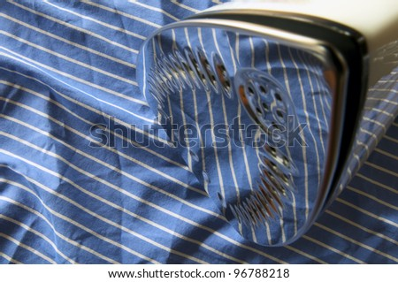 Iron on blue and white striped shirt - stock photo