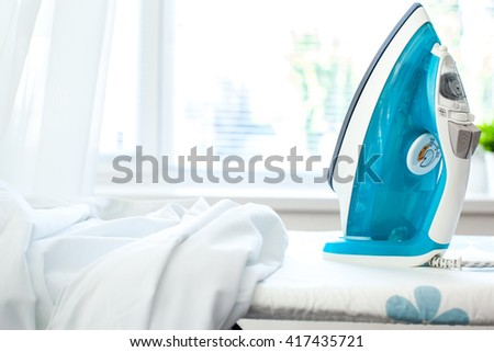 Iron on ironing board on light home interior background - stock photo