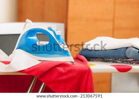 Iron on ironing board with clothes