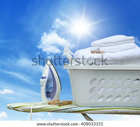 Iron on ironing board with laundry basket - stock photo