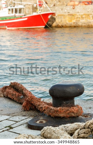 Iron pier in the harbor with a big rope. Vertical image.