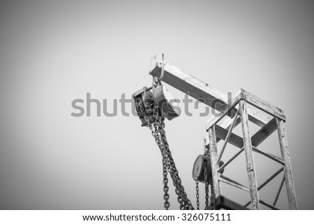 iron pulley on blue sky , black and white - stock photo