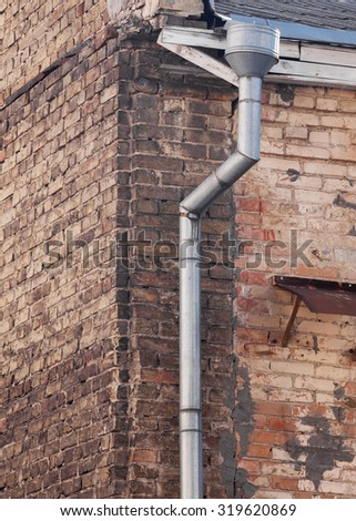 Iron rain gutter on a brick wall  - stock photo