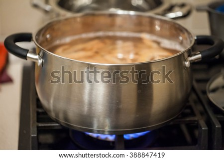 Iron silver pot standing on the gas on the fire on the stove. It boiled shrimp - stock photo