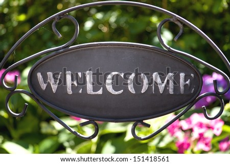 iron welcome sign in the garden with hydrangea on the background - stock photo