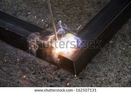 Iron welding with bright light and smoke at manufacturing  - stock photo