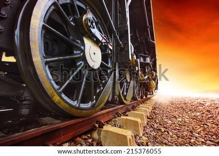 iron wheels of stream engine locomotive train on railways track perspective to golden light forward use for old and classic period land transport and retro vintage style background - stock photo