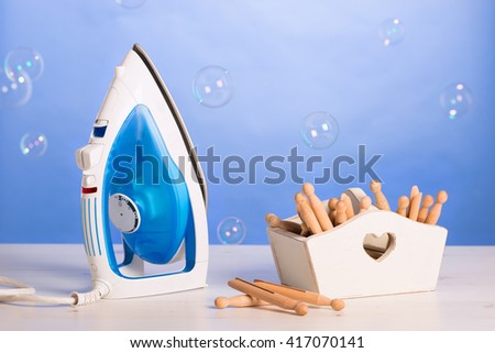Iron with box of pegs with wash day bubbles - stock photo