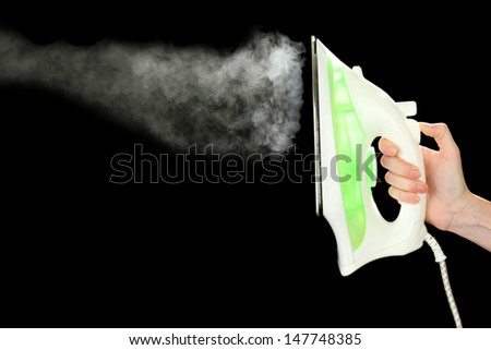 Iron with steam, isolated on black - stock photo