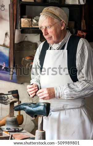 IRONBRIDGE, ENGLAND - JULY 21 2012 : Man dressed as Victorian cobbler  re-enacting shoe mending at Blists Hill Museum set in recreated streets and is a popular tourist attraction.Shropshire, England.