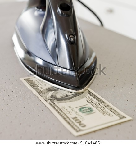 Ironing a Hundred dollar bank note - stock photo