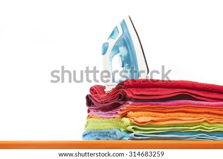 Ironing board with colorful towels on white background - stock photo