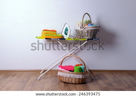 Ironing board with laundry on light background - stock photo