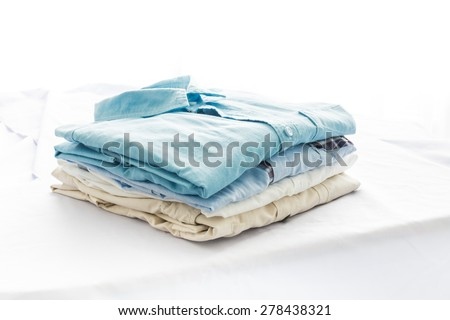 ironing, clothes, housework and objects concept, close up of iron and clothes on table at home - stock photo