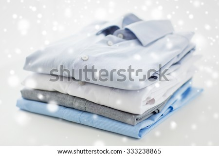ironing, laundry, clothes, housekeeping and objects concept - close up of ironed and folded shirts on table at home over snow effect - stock photo