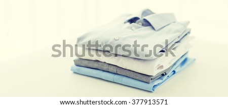ironing, laundry, clothes, housekeeping and objects concept - close up of ironed and folded shirts on table at home - stock photo