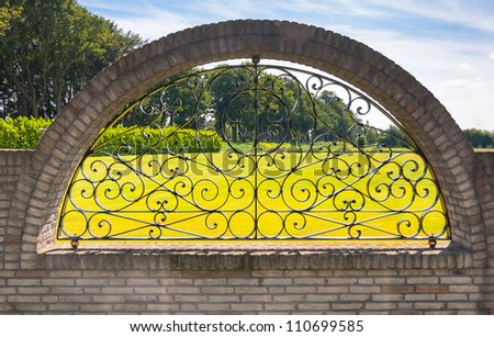 Ironwork fence with curves and a rural background. - stock photo