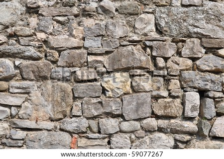 irregular natural stone wall (textured background) - stock photo
