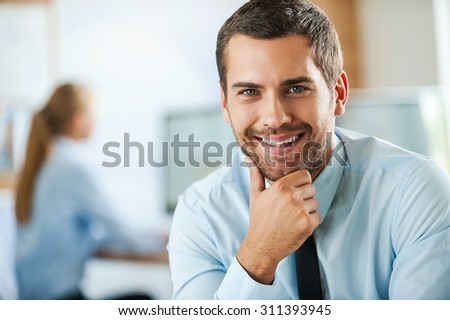 Irresistible corporate charm. Smiling young businessman in formalwear holding hand on chin and looking at camera while his female colleague working in the background - stock photo