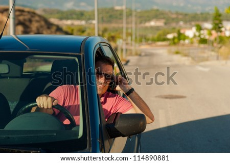 Irresponsible guy using his mobile phone while driving - stock photo