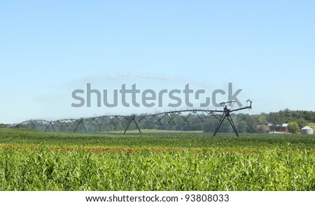 Irrigating a farm field of green soybeans - stock photo