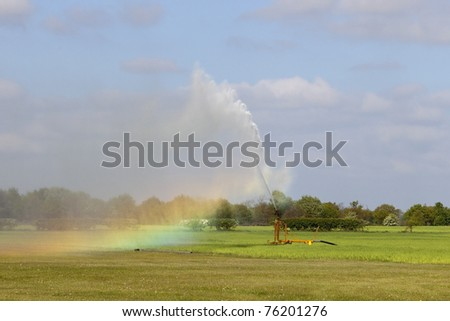 irrigating equipment with water fountain and rainbow under a blue cloudy sky - stock photo