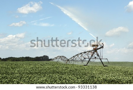 Irrigating farm field of a crop of soybeans - stock photo