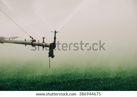 irrigating fields - large agricultural irrigation systems - stock photo