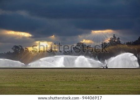 Irrigating Green Grass Polo Field  Irrigation Rain Bird Jets Spraying Water Against A Bad Weather Dramatic Cloudy Sunset Sunrise Sky Watering System Guided By GPS guidance system - antennas receivers