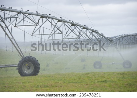 Irrigation by pivot sprinkler and spraying system on misty green grass field or meadow on rural agricultural farm land, copy space. - stock photo