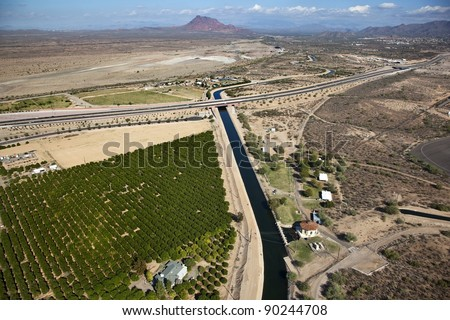 Irrigation canal in the Arizona desert with Red Mountain in the distance - stock photo