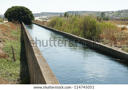 Irrigation canal in the field - stock photo