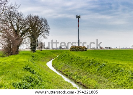 irrigation channel that passes through the cultivated fields next to cell phone trellis in Italy - stock photo