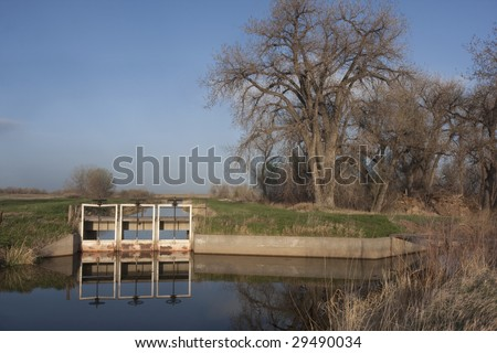 irrigation ditches with flowing water in northern Colorado, three headgates, lifting gear and foot bridge, spring time with green grass and cottonwood trees