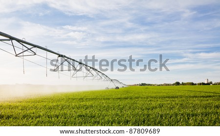Irrigation pivot watering a a green crop. - stock photo