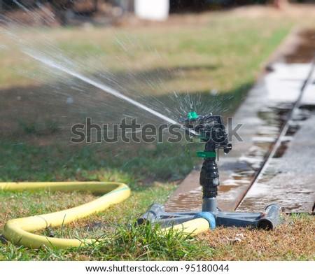 Irrigation sprinkler watering grass. - stock photo