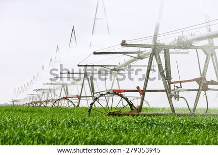 irrigation system on a green field in agriculture to increase crop - stock photo